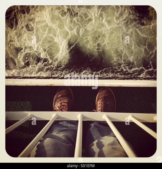 A man standing on the deck of a ship in a storm staring down into the waves POV - Stock-Bilder