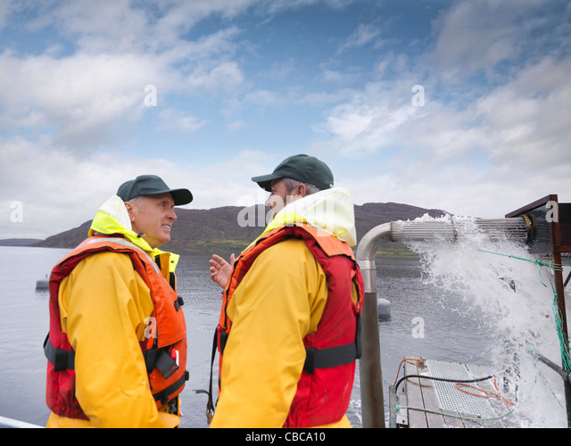 Fishermen talking on boat - Stock Image