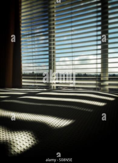 Window venetian blinds casting shadows on bed - Stock Image