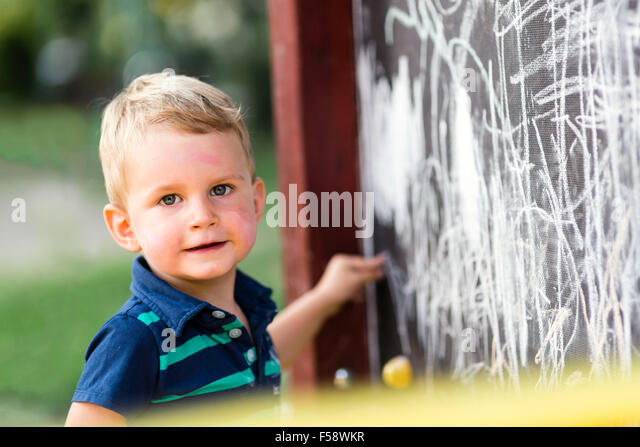 Creative cute toddler drawing with chalk outdoors - Stock-Bilder