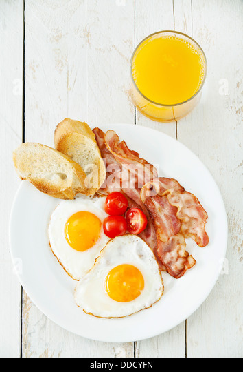 Traditional breakfast eggs with bacon - Stock Image