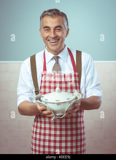 Handsome smiling man in apron serving dinner in a tureen - Stock Image