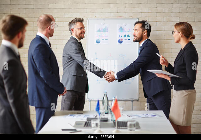 Foreign business partners greeting one another by handshaking - Stock Image