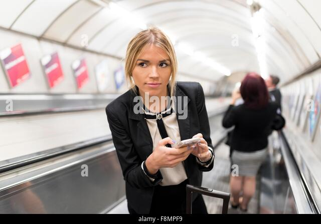 Businesswoman texting on escalator, London Underground, UK - Stock Image