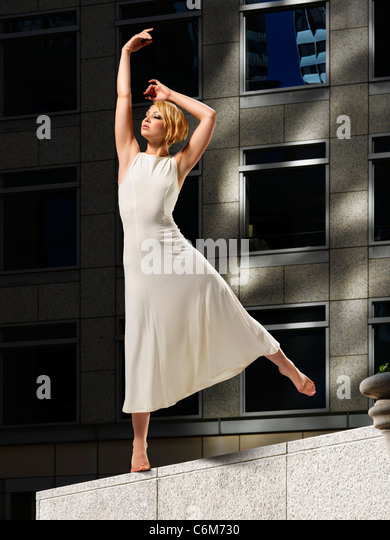 woman dancer in bright sunshine posed on stone ledge of office building plaza seen dramatically against dark building - Stock Image