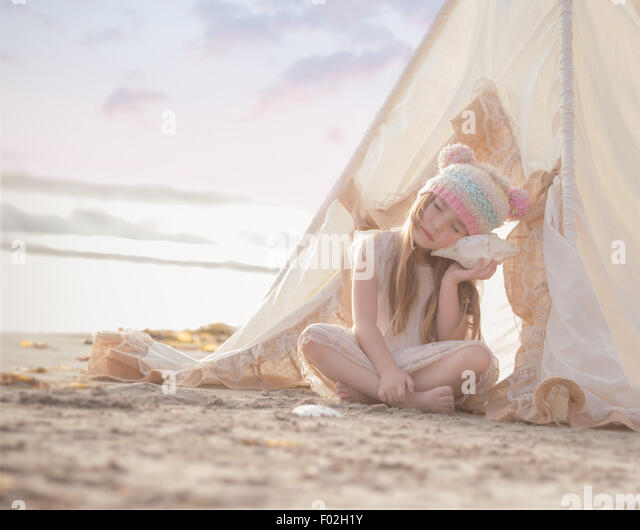 Girl sitting in a wigwam on the beach listening to a seashell - Stock Image