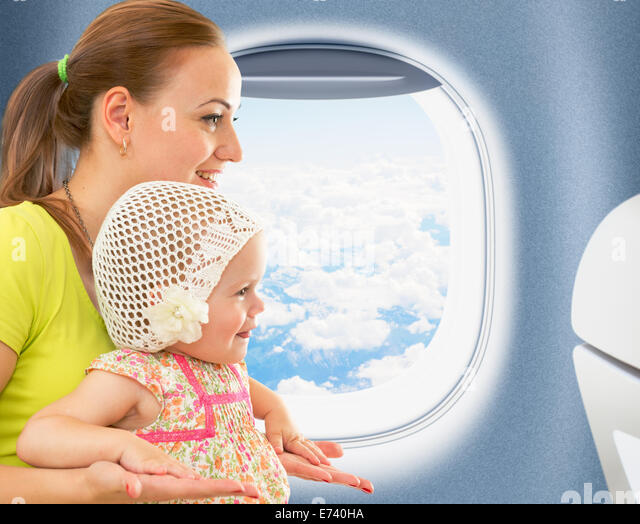 Happy mother and kid traveling together in aeroplane cabin near window - Stock-Bilder