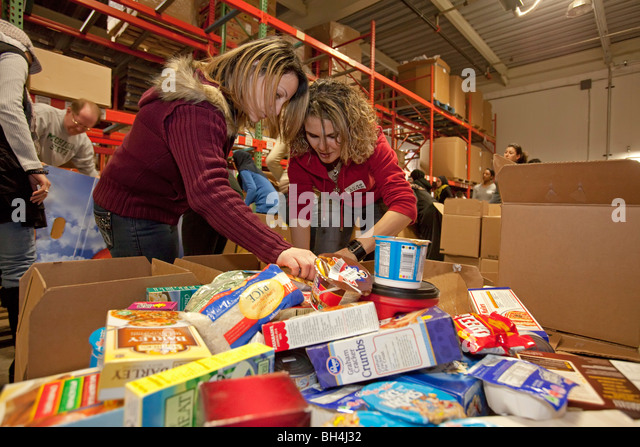 Volunteers Pack Food at Community Food Bank - Stock Image