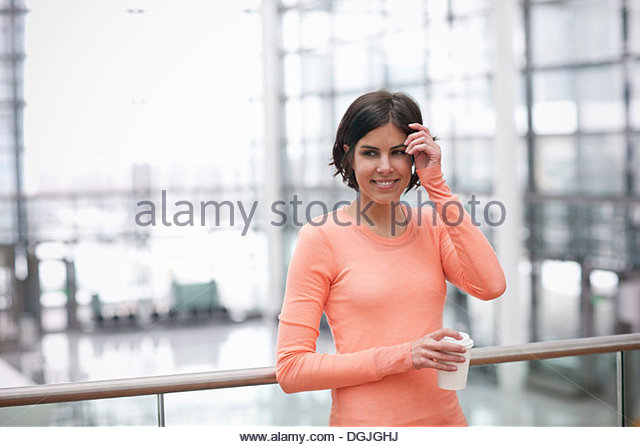 Candid portrait of young female with coffee - Stock Image
