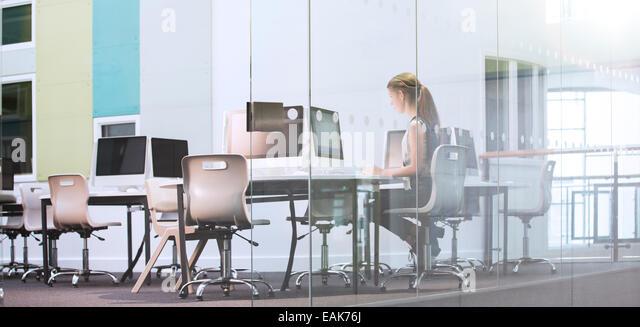 Teenage girl using computer in computer room - Stock Image