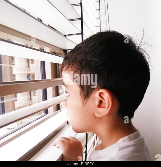 Portrait of a boy looking through the window - Stock Image