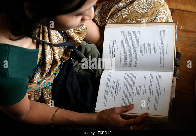 Woman reading the Bhagavad Gita, Sarcelles, Val d'Oise, France, Europe - Stock Image
