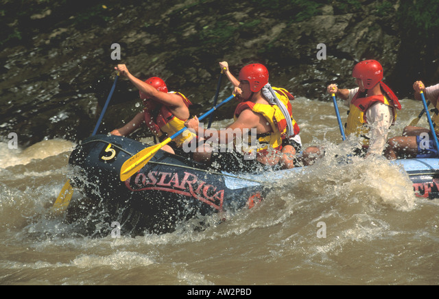 costa rica whitewater rafting action men digging in paddles getting splashed on the lower pacuare river - Stock Image
