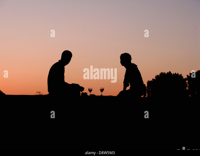 A young couple silhouetted by the evening sky, sitting on a wall with glasses of wine, Arles, France - Stock Image