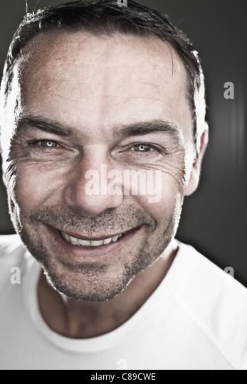 Close up of mature man against black background, smiling, portrait - Stock-Bilder