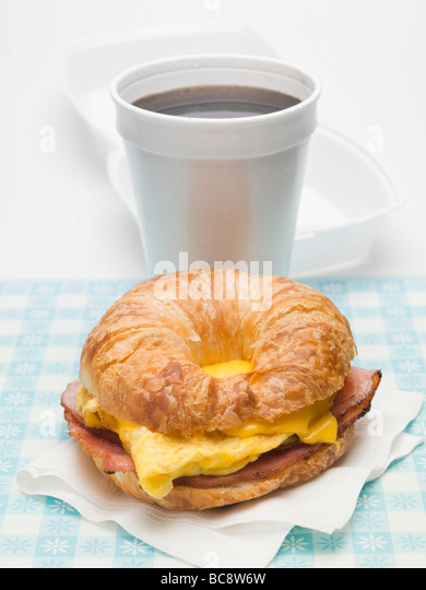 Croissant with scrambled egg, cheese & bacon, cup of coffee - - Stock Image