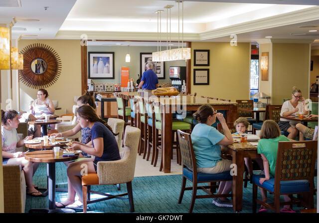 Florida Ellenton Hampton Inn hotel lodging Hampton by Hilton Hampton Inn hallway woman guest free breakfast dining - Stock Image