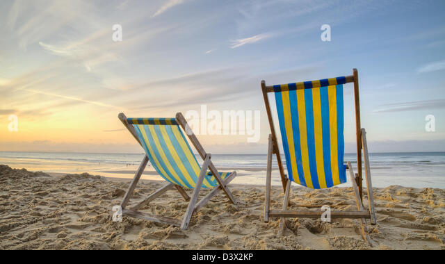 Two empty deck chairs on a beach at sunrise - Stock Image