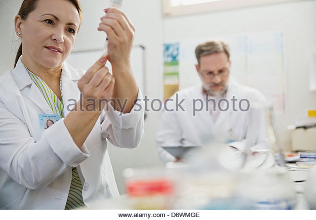 Mature female technician filling syringe with male colleague working in background - Stock Image