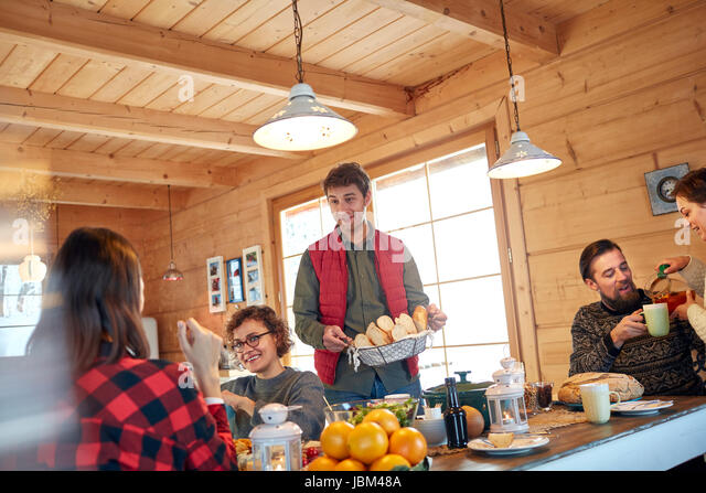 Friends serving and eating food in cabin - Stock-Bilder
