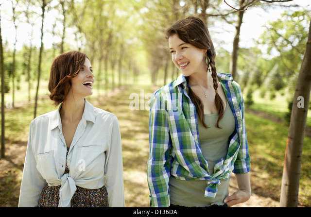 Two young women walking down an avenue of trees - Stock Image