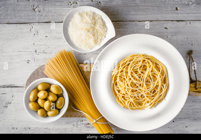 Raw and cooked spaghetti with olives and cheese on the white wooden table top view. Concept of Italian cuisine - Stock Image