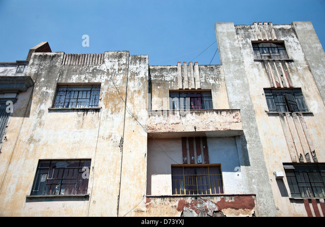 melancholy beautiful sadly decayed badly maintained facade of Art Deco apartment building on a sunny spring day - Stock Image