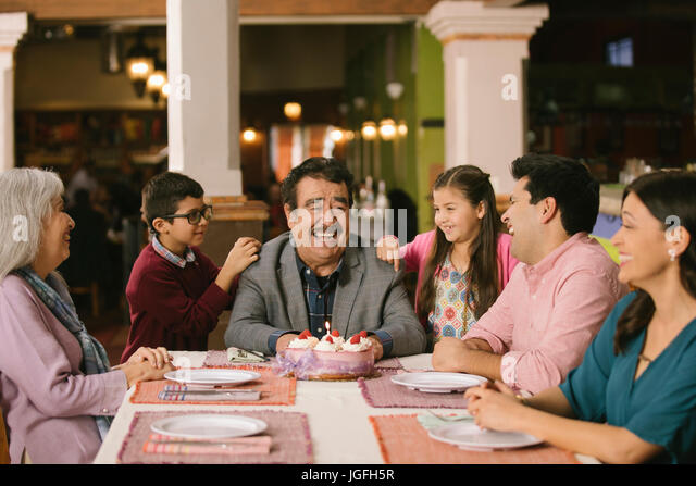 Family celebrating birthday or older man in restaurant - Stock Image