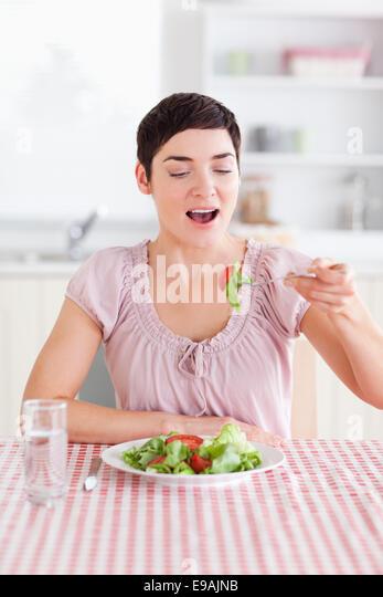 Joyful brunette woman eating salad - Stock Image