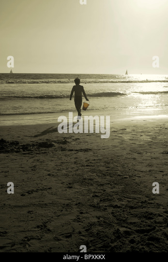 sepia image of boy running on beach with bucket near the ocean - Stock Image