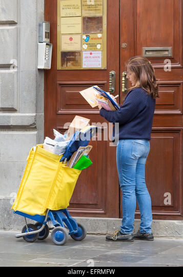 Female Spanish Postal worker delivering mail to business address - Stock Image