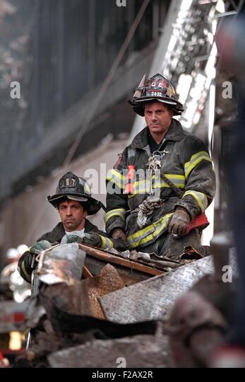 NYC Firemen, grim and geared for rescue/recovery work at the destroyed World Trade Center, NYC. They have a high - Stock-Bilder