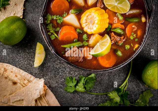 Autumnal vegetable stew. Mexican traditional vegetable soup Mole de olla with meat, potatoes, carrots, beans, corn - Stock Image