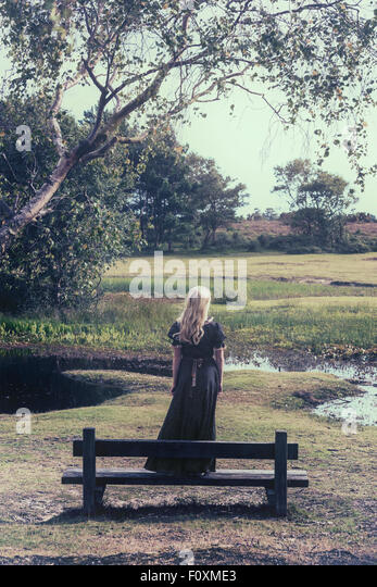 a blonde girl in a floral dress is standing on a bench at a pond - Stock Image