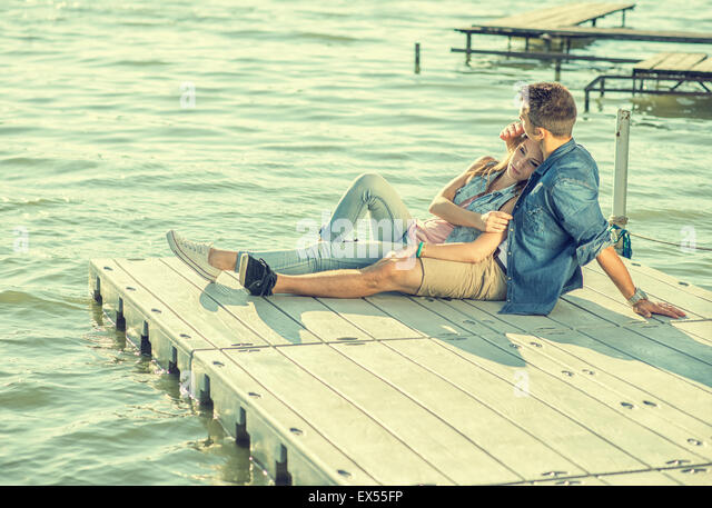 Couple in love sitting on the pier, embrace - Stock Image