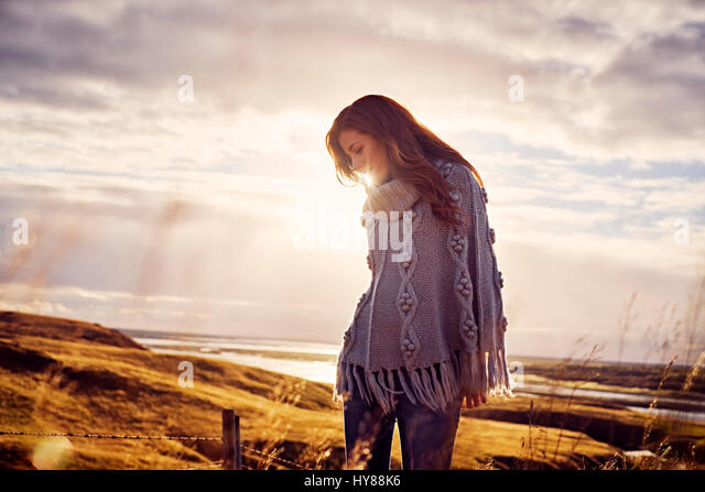 A young women wearing knitwear standing in a dramatic landscape in Iceland - Stock Image