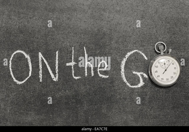 on the go phrase handwritten on chalkboard with vintage precise stopwatch used instead of O - Stock-Bilder