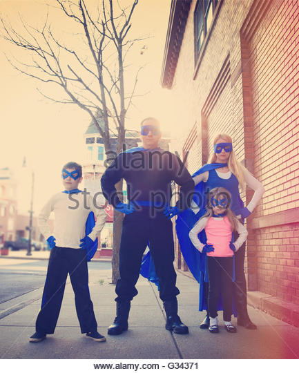 A young super hero family are standing outside with blue capes and masks for a protection, strength or happiness - Stock Image