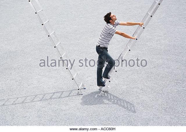 Man climbing ladder outdoors - Stock-Bilder