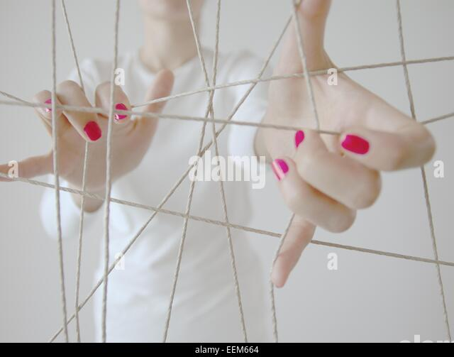 Woman's hands and cat's cradle rope - Stock Image