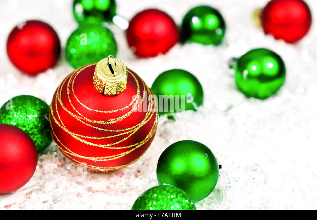 Red and green Christmas ornaments on snow background - Stock Image