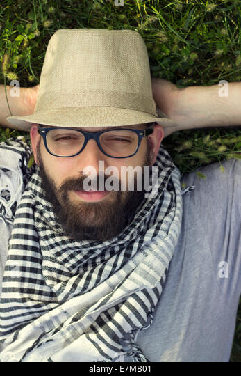 Portrait of a bearded smiling young hipster man lying in the grass and daydreaming - Stock-Bilder