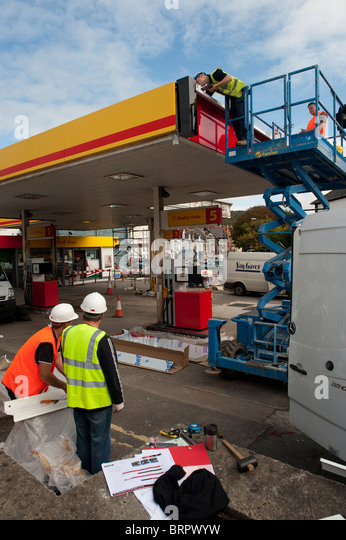 Workmen Renovating and rebranding a Shell petrol station garage as Texaco , UK - Stock Image