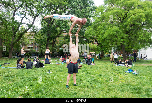 Gymnastics in Washington Square Park -- Two men preforming a hand balancing gymnastic lift outdoors in New York - Stock Image