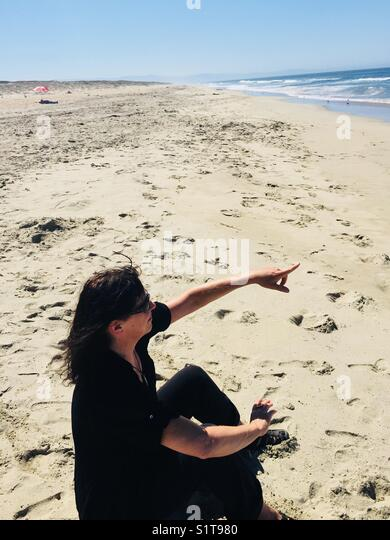 Woman on beach pointing to whales - Stock Image