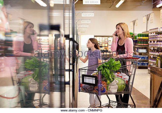 Mother and daughter shopping in supermarket - Stock Image