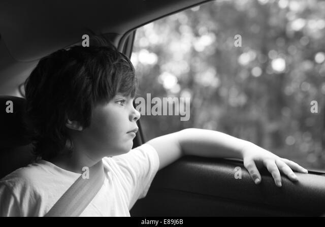Boy lost in thought in the car, roadtrip - Stock-Bilder