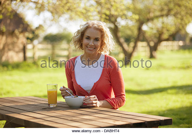 A mature woman sitting at a garden bench eating breakfast - Stock Image