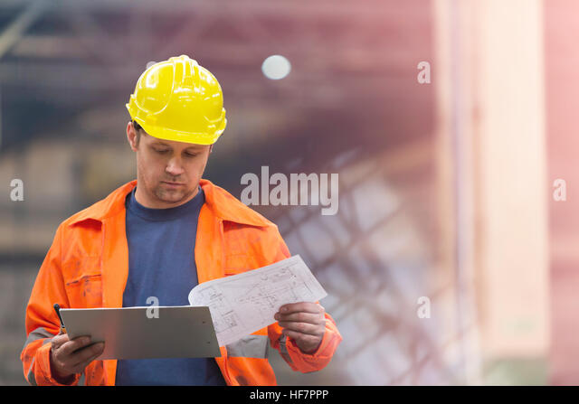 Steel worker reviewing blueprints in factory - Stock Image