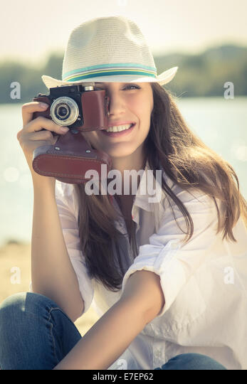 Young hipster girl with old film camera at the beach. Summer vacation background - Stock-Bilder